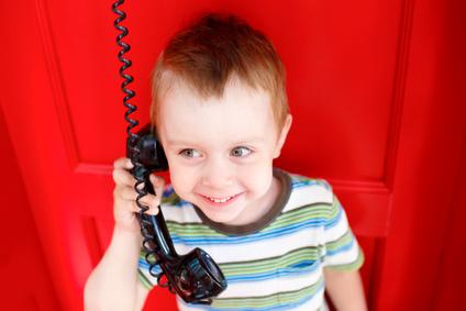 Zdjęcie chłopca trzymającego słuchawkę telefoniczną